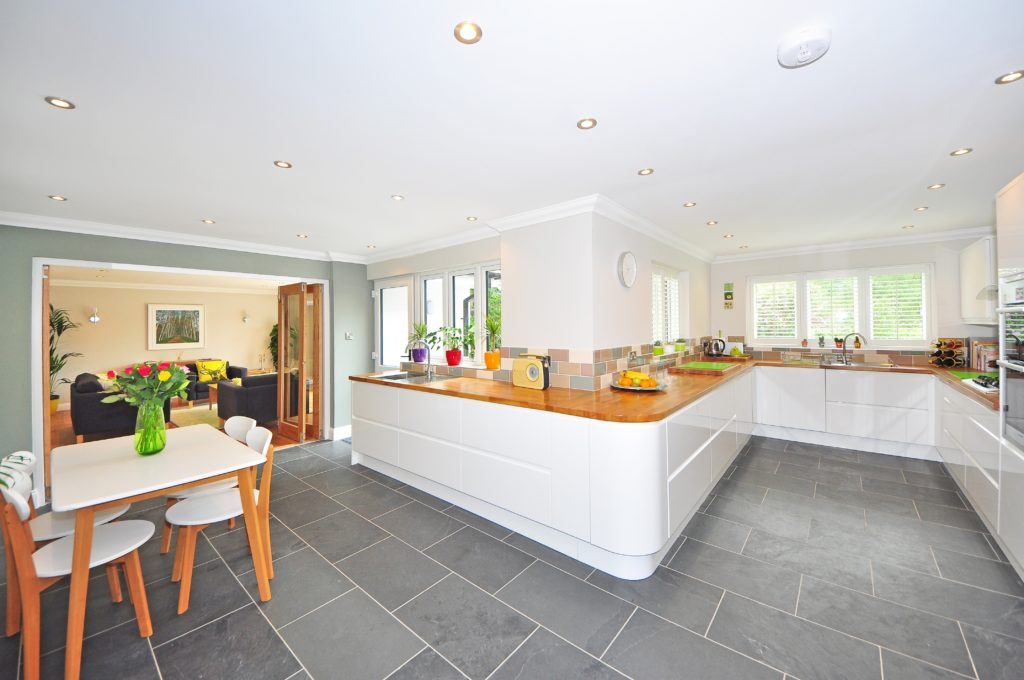 Wide kitchen with white cabinets and grey flooring
